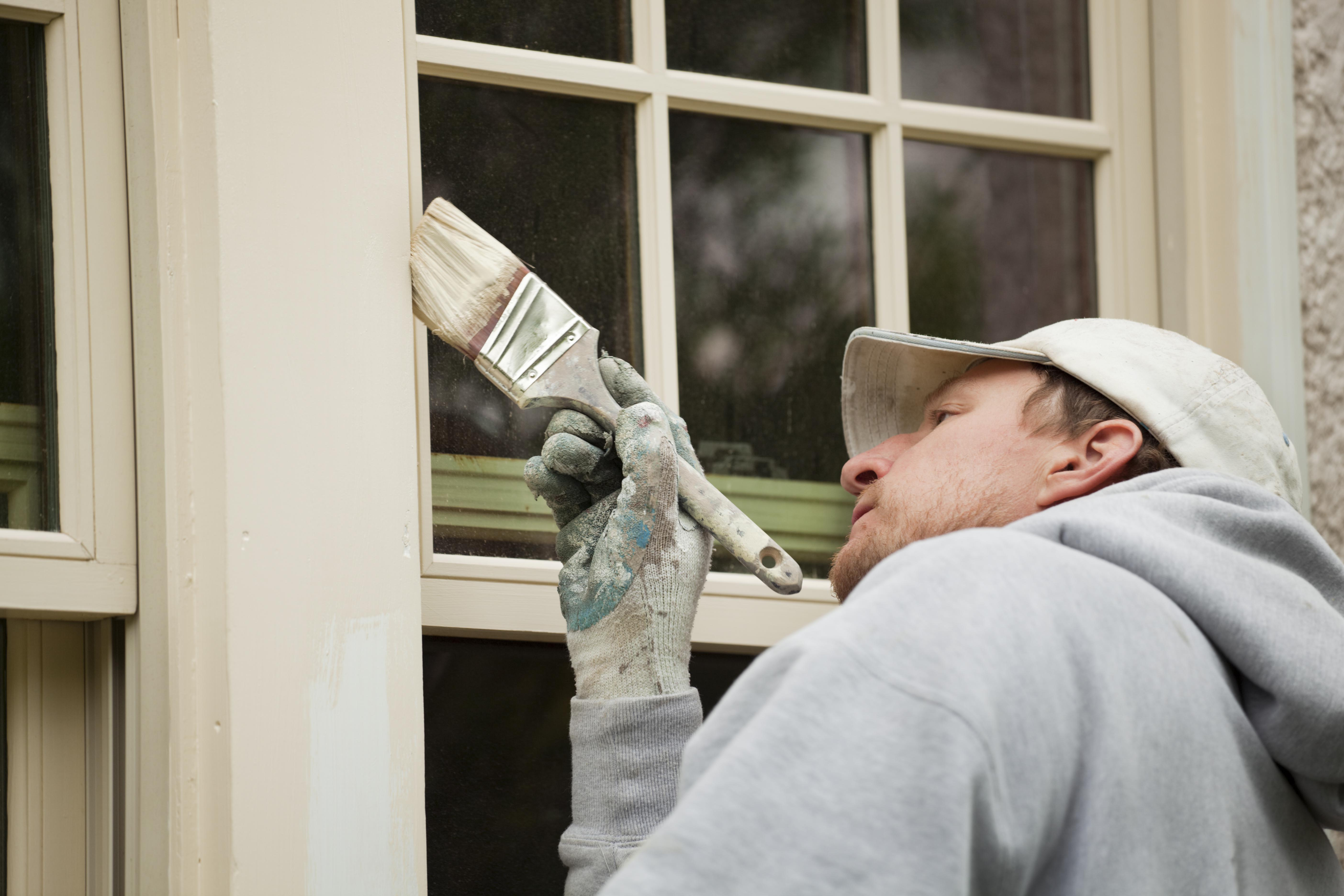 Painter treating and painting external windows